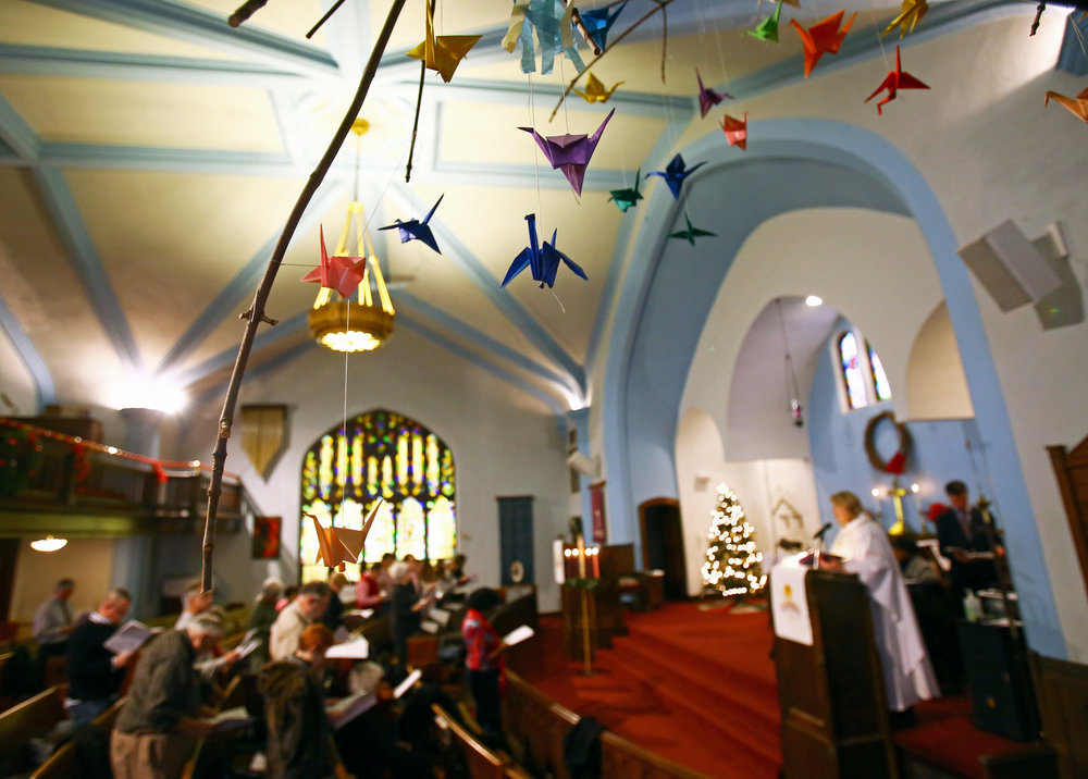 Origami swans hang in the sanctuary of the Redeemer Lutheran Church created by the kids in the churches summer program during the Redeemer Lutheran Church Christmas Eve service in Toledo, Oh. on Saturday, Dec. 24, 2016.