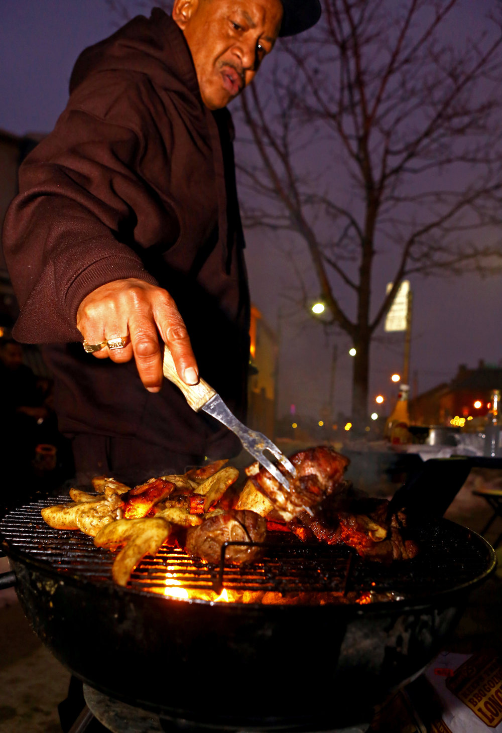 """Chet Mason of Toledo grills chicken on a charcoal grill on the sidewalk at the intersection of Adams Street and 16th Street for anyone who wants something to eat in Toledo, Oh. on Saturday, Dec. 24, 2016. Mr. Mason said """"Me selling food is a sin"""" and went on to say that he typically cooks food on to give away throughout the year."""