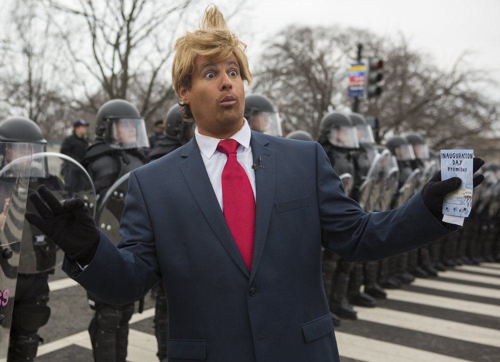 A Donald Trump impersonator poses in front of a line of police in riot gear on First Street NE to block a group of protesters during the inauguration ceremony in Washington D.C. on Friday, Jan 20, 2016.