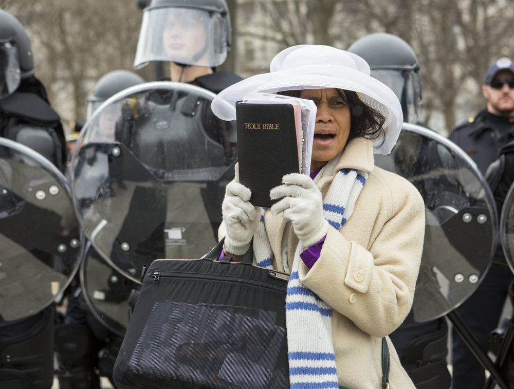 Evangelist Mary Clement of Silver Spring, Md. reads scripture while pacing in front of riot police blocking First Street NE from a group of protesters during Donald Trump's inauguration ceremony in Washington D.C. on Friday, Jan. 20, 2016.