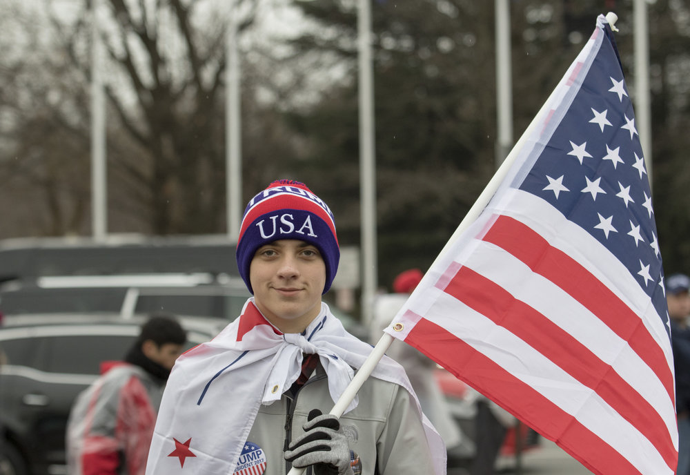 """Young Patriot"" of West Virginia stands with an American Flag in and watches the protest after the 58th inauguration ceremony in Columbus Circle in Washington D.C. on Friday, Jan. 20, 2016."