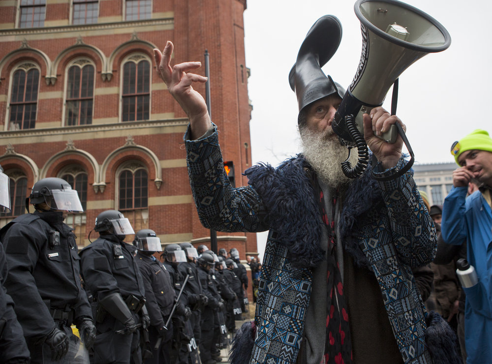 Performance artist and activist Vermin Supreme speaks to the crowd gathered on the intersection of K Street NW and 13th Street blocked by riot police after a violent protest broke out earlier in the day on Friday, Jan. 20, 2016.