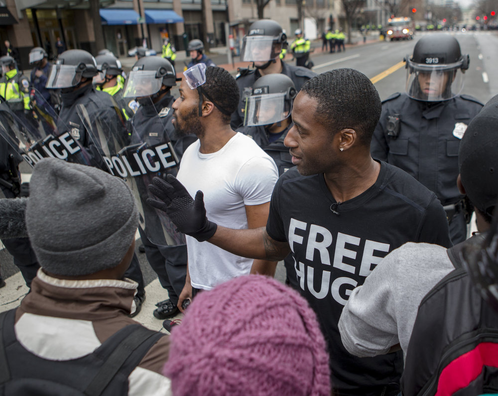 Free Hugs Project activist Ken Nwadike of San Diego stands between a crowd of protesters and riot police on at the intersection of K Street and 13th Street NW to help prevent further violence shortly after Donald Trump's inauguration ceremony in Washington D.C. on Friday, Jan. 20, 2016.
