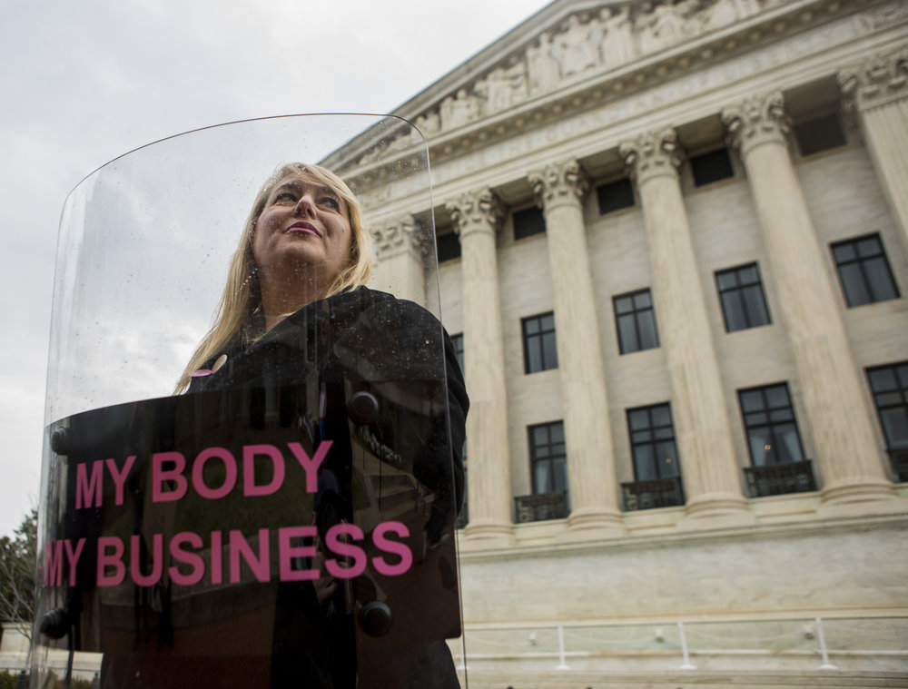 "Performance artist Michele Pred of San Francisco poses with her ""My Body My Business"" riot shield piece by the Supreme Court of the United States in Washington D.C. On Friday, Jan. 20, 2016."