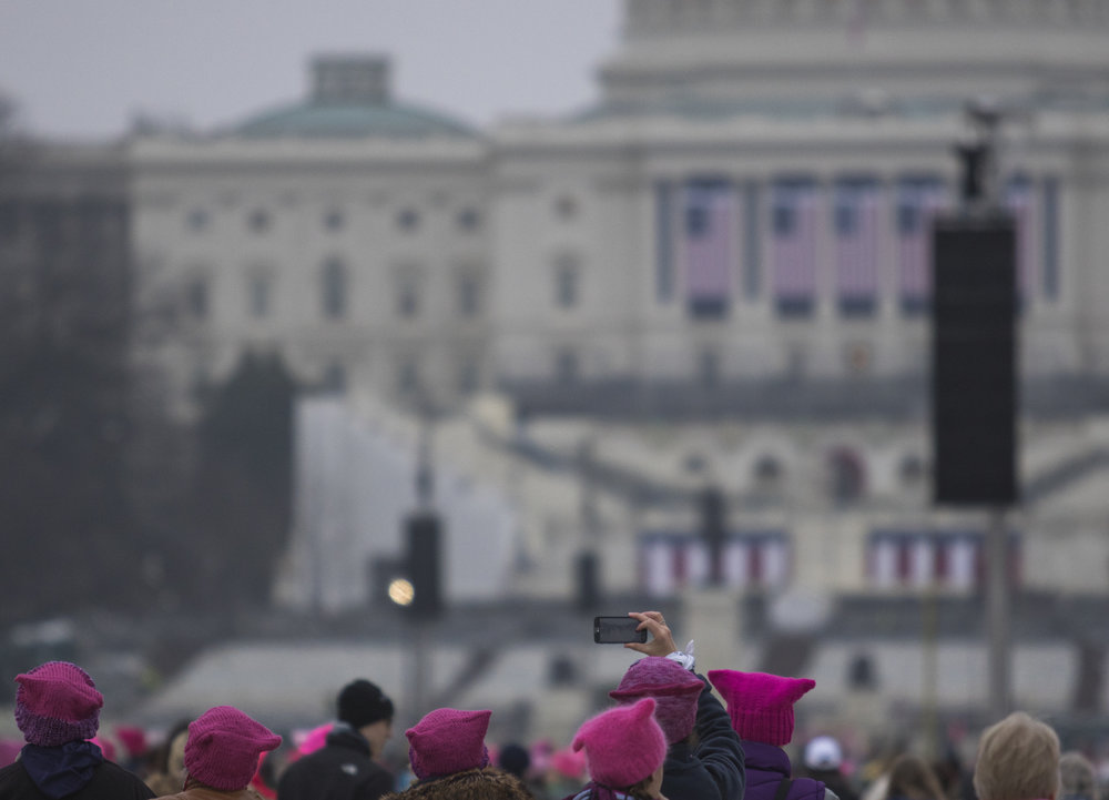 A Women's March on Washington   participant snaps a photo of the Capitol Building as crowds mass onto the National Mall early on Saturday, Jan. 21, 2016.