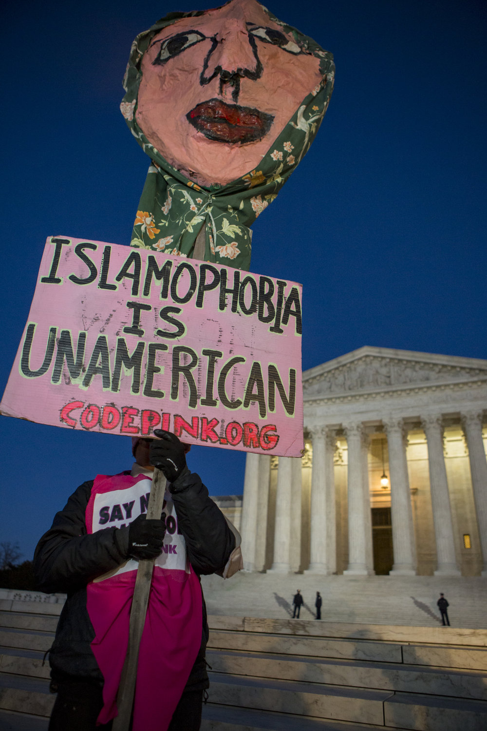A protestor holds a sign on the steps of the Supreme Court during the rally organized by democratic lawmakers against President Trump's recent executive orders.