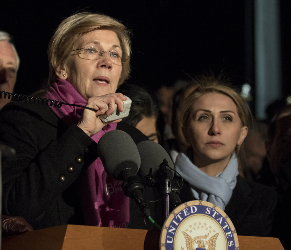 Senator Elizabeth Warren (D-Ma.) speaks out against President Trump's recent executive orders with Farah  Amer  Kamal, right, of Iraq who is now barred from returning to her home country to visit her husband and father.