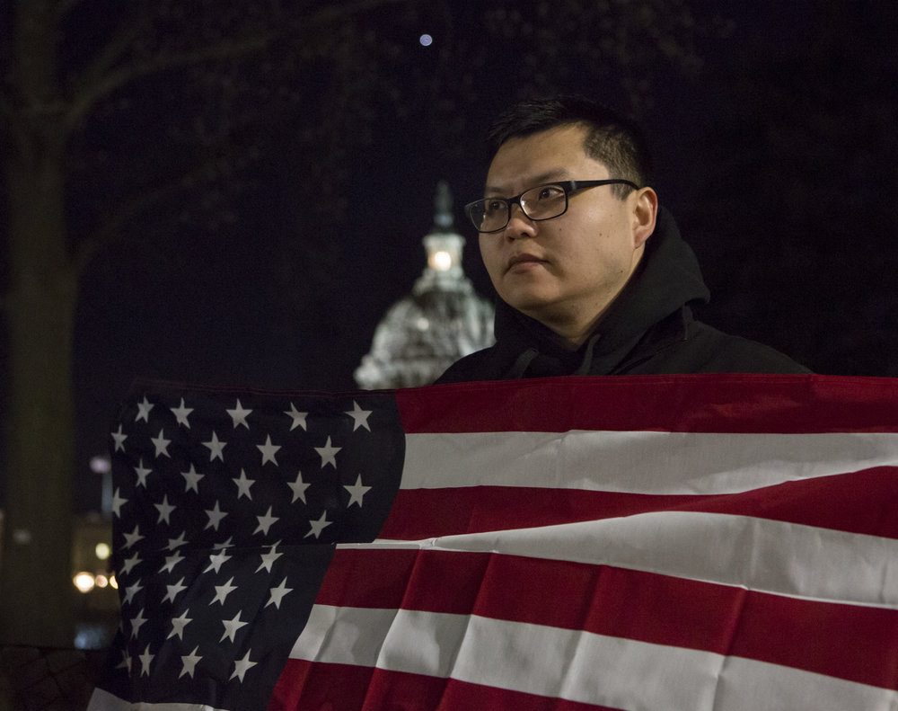 Perry of Washington D.C. holds an American flag on First Street NE during the rally. Perry is a law student and naturalized citizen after immigrating from China. He said he came out to the rally to stand together with the other immigrants.