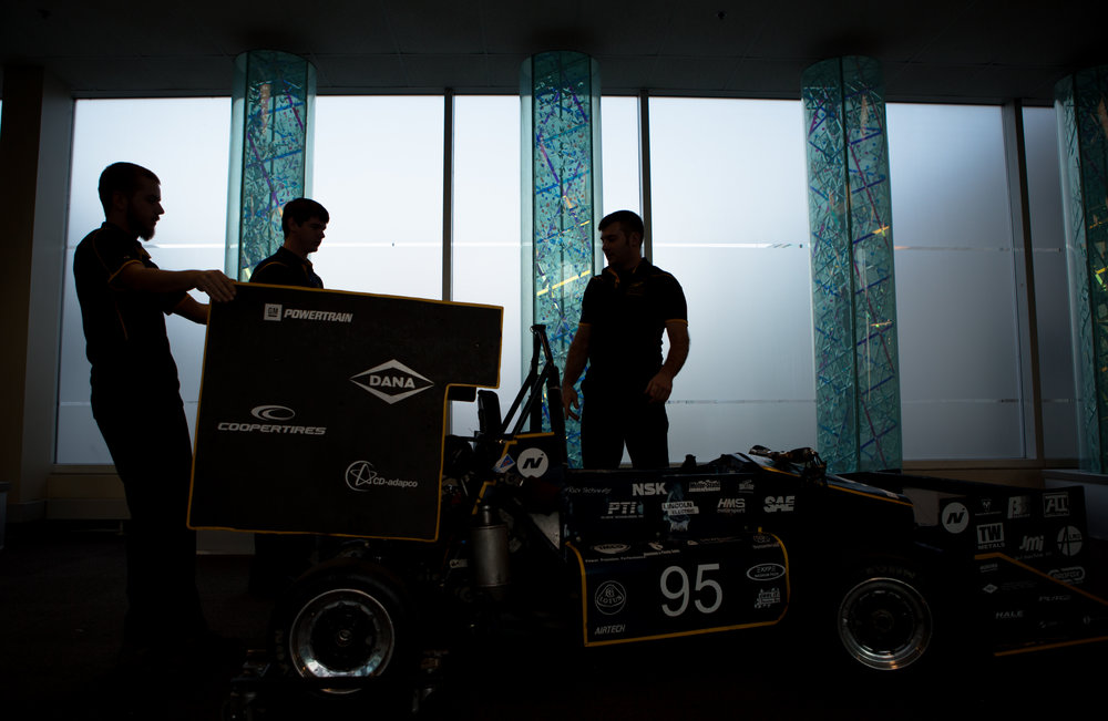 From left, Jared Schaufele, Josh Remmetter, and Dustin Moosman wheel the 2015 season Formula SAE car through the lobby of the University of Toledo's North Engineering Building for a team photo.