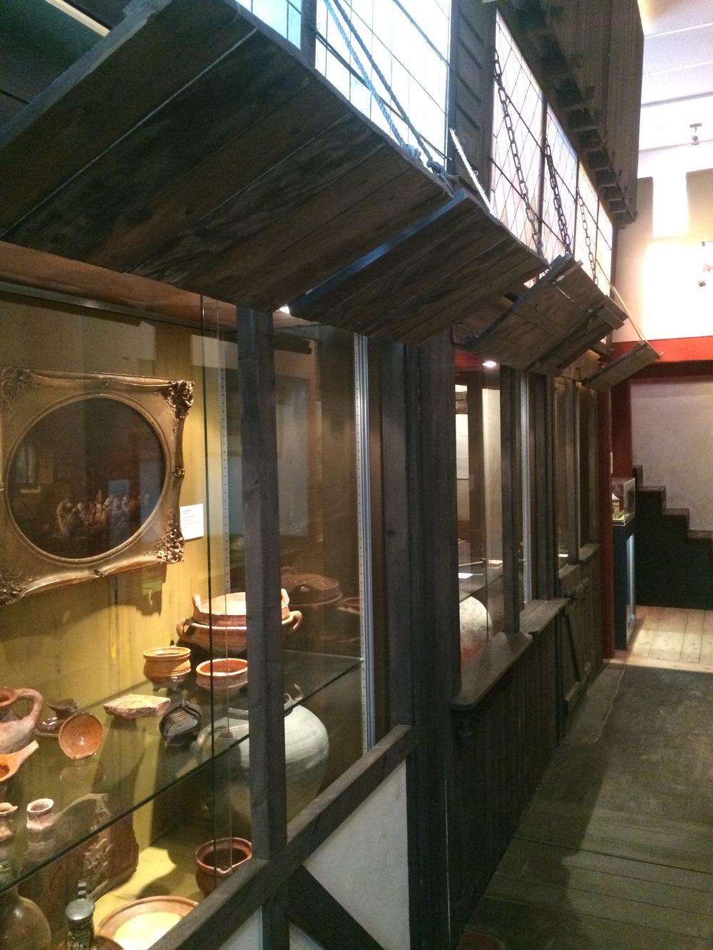 In de 'ramen' van het middeleeuwse straatje worden voorwerpen getoond.