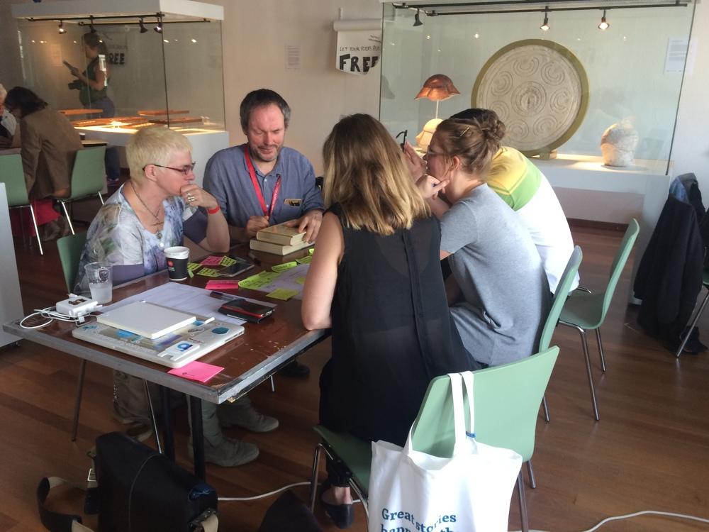 Een groepje praat met een conservator over hun object.