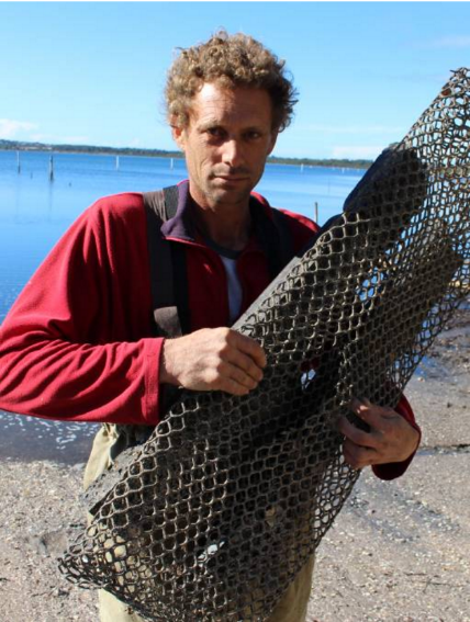 Frustrated: Dominic Boyton of Merimbula Gourmet Oysters holds up bag that has been slashed with a knife in order to steal the oysters inside. Picture: Melanie Leach