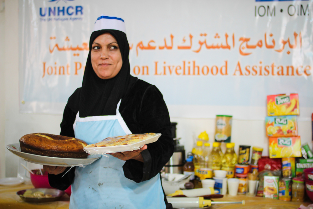 An Iraqi woman holds her baked goods during a cooking class, Baghdad / For the Iraq mission of the International Organization for Migration