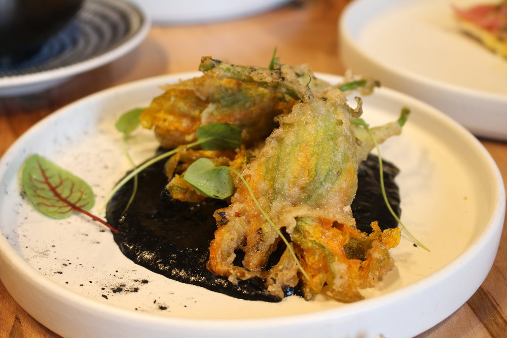 Stuffed squash blossoms with squid ink romesco
