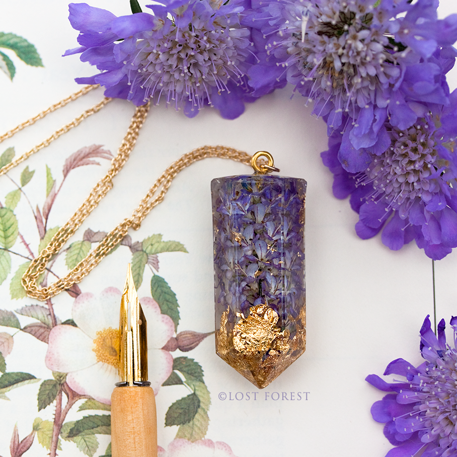 custom necklace: hebe caledonia crystal quartz & gold leaf - I'm completely in love with the gorgeous necklace!! What a beautiful and unique necklace, LOVE this in every way, the feel, colour of purple and gold, hexagon pointed shape, natural flowers!! Just Perfect!I have been wearing it today all day, and took it in my hand and stared at it for many times as it's too lovely and really well made. This is my first resin pendant, I haven't seen like this and I'm so very happy, I'll wear it very often!The artist must be so talented as it looks very difficult to finish like this beautifully without tiny bubbles. I'll cherish it for many years to come for sure!!- Mai, Japan