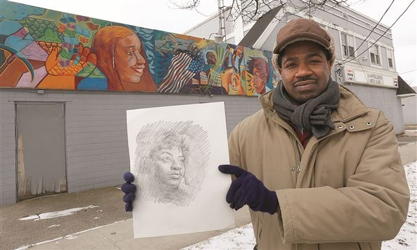 Yusuf Lateef holds a drawing of the late artist Patrice Davis while standing in front of his first mural.  THE BLADE/LORI KING