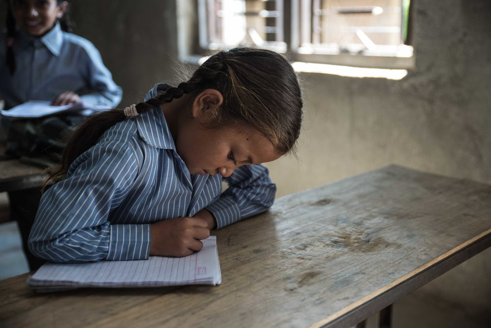A young girl working in one of our THISWORLDEXISTS education projects in Nepal.