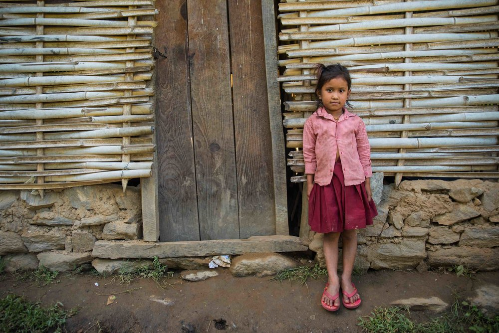 A young girl poses outside her old school in Sorung Chhabise, Nepal. THISWORLDEXISTS are currently constructing a new facility to ensure the school can cater to all students in the area.