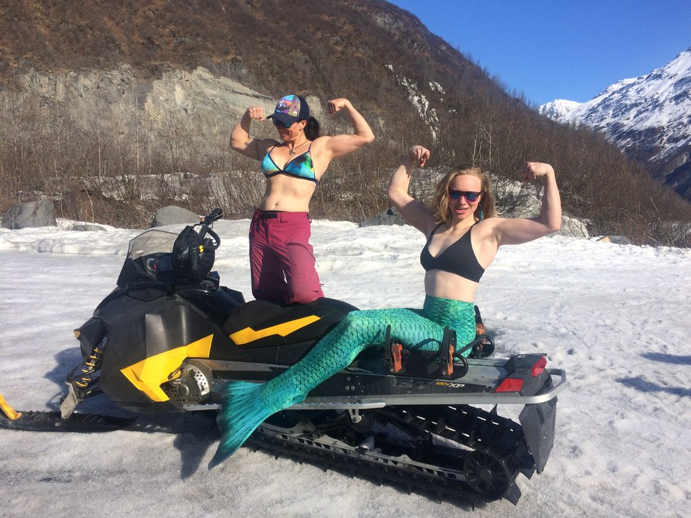 """Suns out, guns out! Pictured at left, Jennie """"Adrenajen"""" Milton, drone pilot and lead safety; Teal Rogers, professional mermaid, aerialist, and mistress of stoke."""