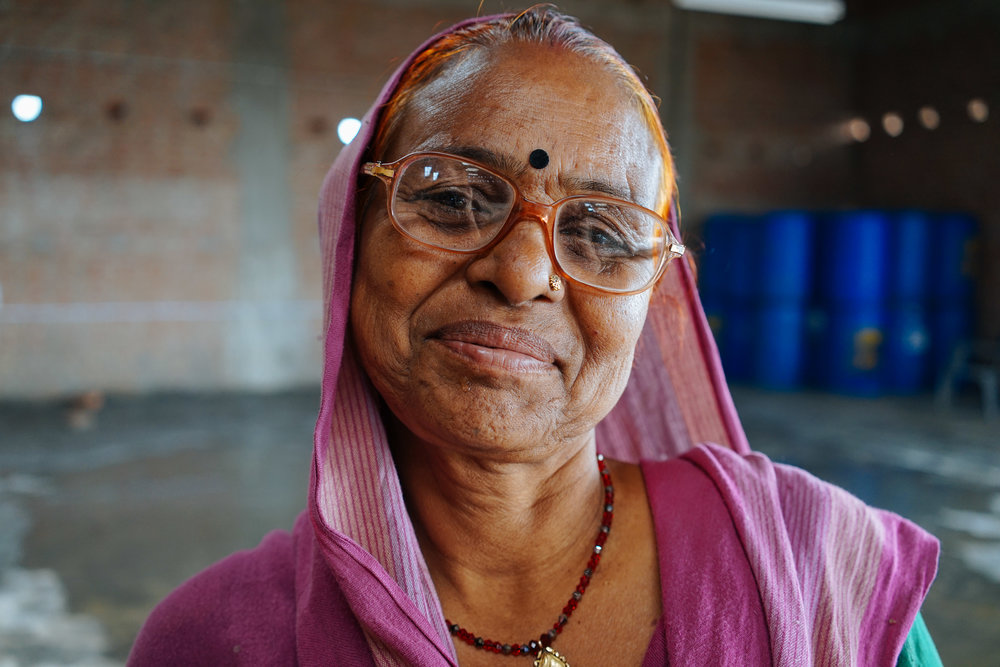 Rani, a woman who works alongside her daughter-in-law at the factory, smiles during her lunch break. The female employees are given filtered drinking water, toilet facilities and multiple breaks throughout the day - benefits they have never found in their other jobs.