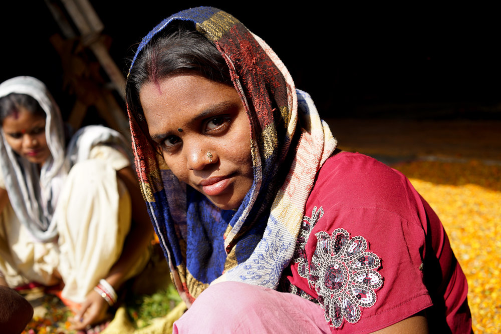 Kamla, who works with her mother-in-law Rani at the factory, sits in the sun to sort flowers.