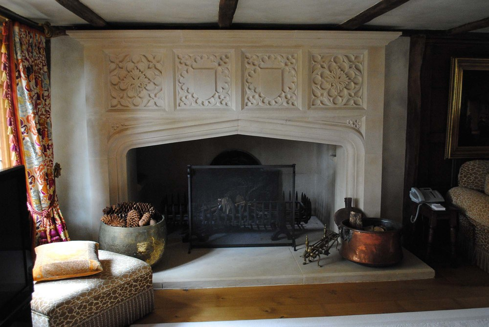 Portland stone fireplace with hand carved Gothic style quatrefoils and shields