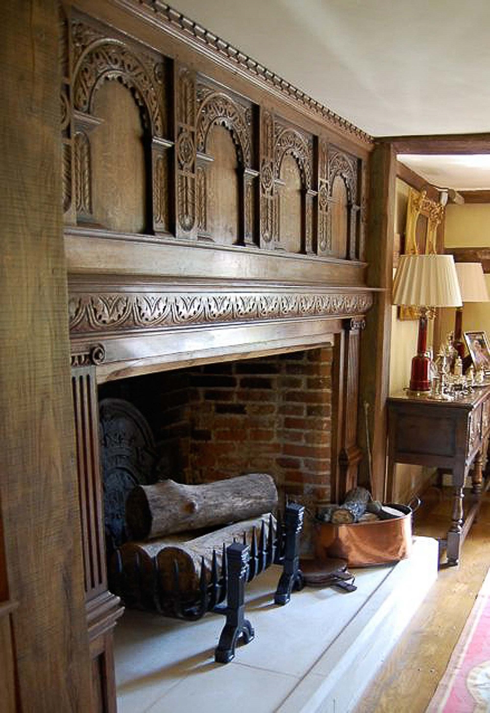 16th and 17th century style oak panlled fireplace with highley decorative carved arches