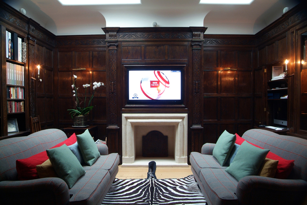 Oak panelled fire surround with hidden Tv reveal panel, in a 17th century country house style