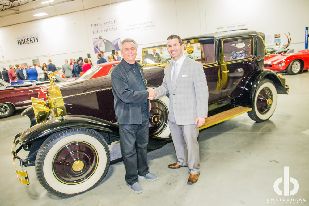 SIR ALFRED J DIMORA, CEO OF DIMORA MOTORCAR, SHAKING HANDS WITH NINO VENTURELLA, CEO OF CRUISE 4 KIDS. THE VEHICLE BEHIND THEM IS A BURGANDY 1931 ROLLS ROYCE PHANTOM II WITH GOLD PACKAGE THAT WAS DONATED TO CRUISE 4 KIDS IN 2014. PHOTO BY: CHRIS BRAKE PHOTOGRAPHY