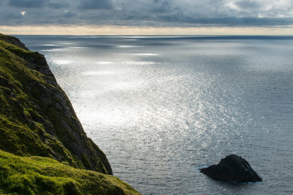 Western coastline and sunlight dappling North Atlantic Ocean, Hermaness National Nature Reserve, Unst, Shetland Islands, Scotland