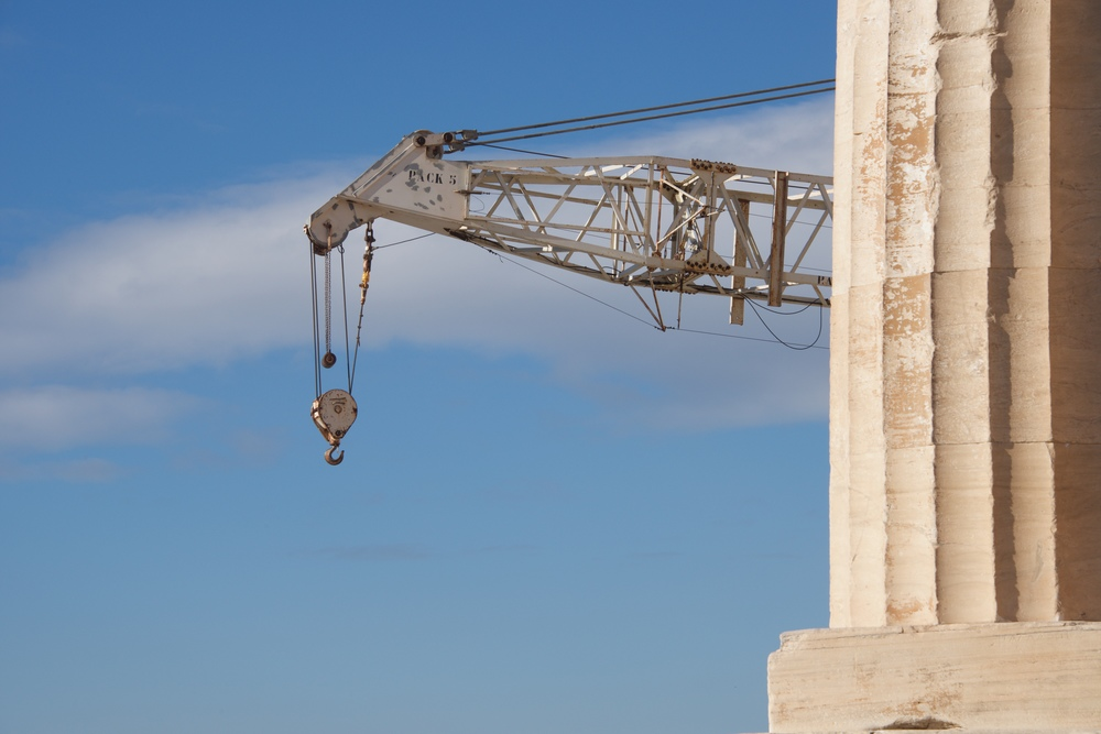 Crane appearing from behind marble Parthenon column.jpg