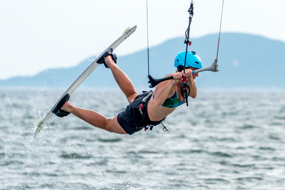 Close-up of female kite surfer getting air
