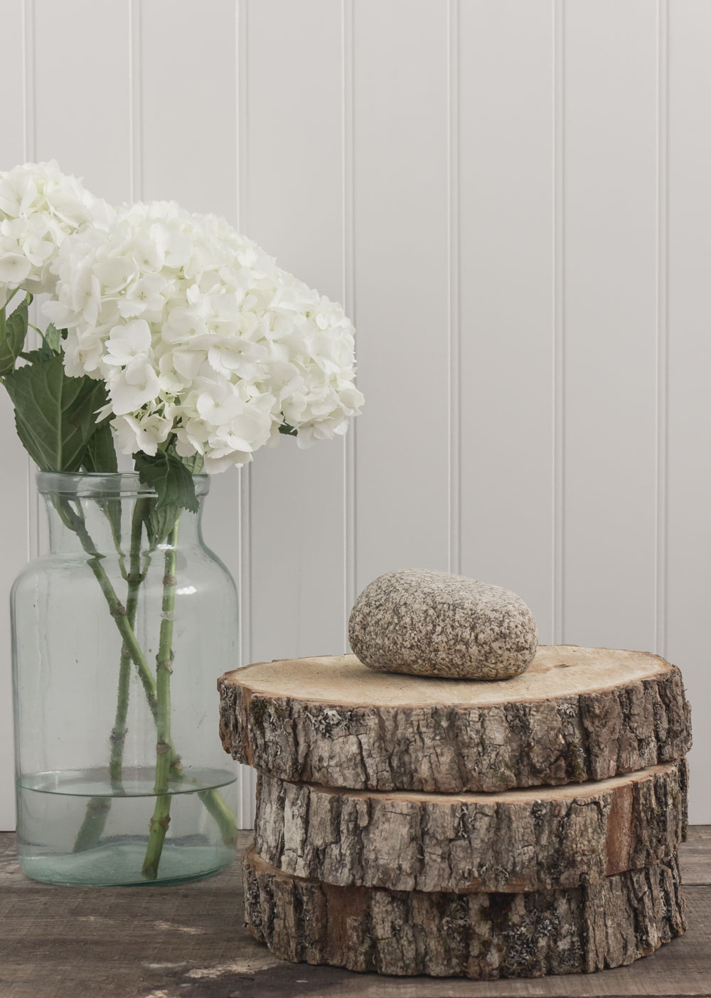 maple tree slices stacked up as a display with a rock