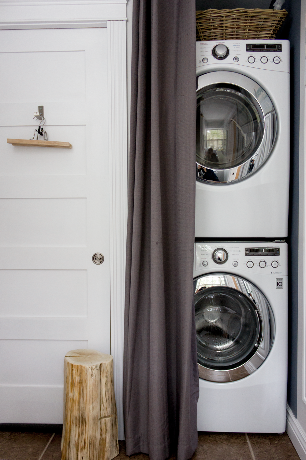 using a curtain and tension rod to hide a stackable washer dryer in bathroom