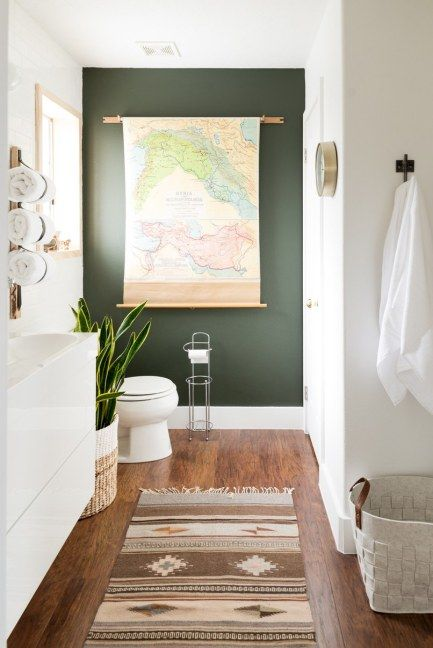 Dark green focal wall in bathroom via Architectural Digest