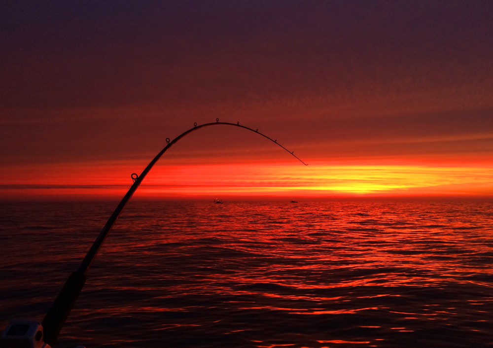 Red skies before sunrise as seen from the kayak of Tom, Mike and Kalvin can be seen fishing in deeper water under his starboard rod.