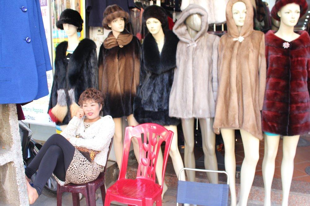 A coat seller talks on her phone, Hanoi