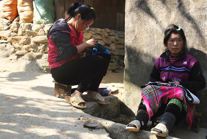 Women embroider outsider their home, Sa Pa