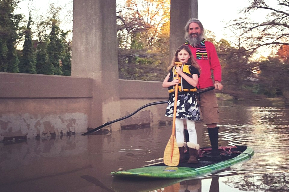 John Ruskey pilots a SUP with a young protégé.