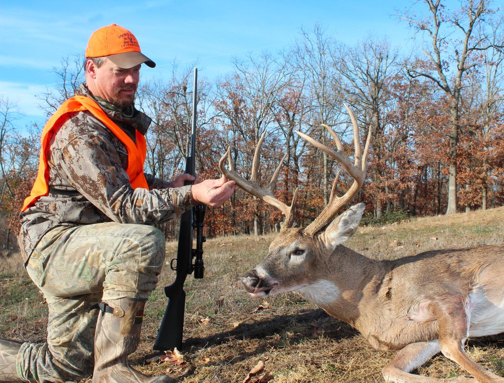 Scoring white-tailed deer has become a popular pastime among Arkansas hunters. Here, hunter Ronnie Cartwright of Greenland checks the antlers on a 140-inch white-tailed buck.
