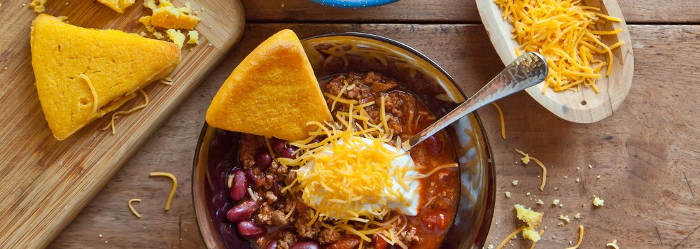 Homemade cornbread, sour cream and cheese are the perfect toppings for a heaping bowl of buffalo chili