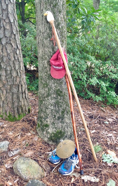 Three essentials Phelps uses on his hiking adventures: baseball cap, tennis shoes, and a hiking stick Phelps was gifted to commemorate his service to Keep Arkansas Beautiful.