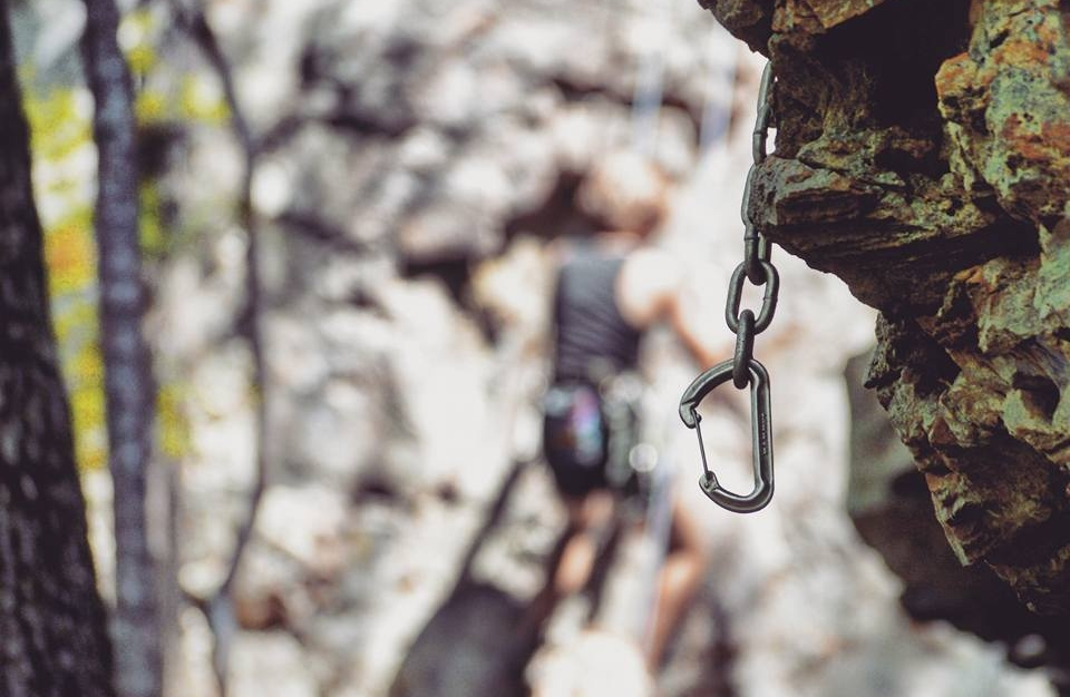 "A carabiner hangs from a bolt on a newly created route at Jamestown Crag near Batesville. Facing page: Bill ""Fitz"" Fitzgerald, an avid climber from Little Rock, scales ""Pagan on Sunday."""
