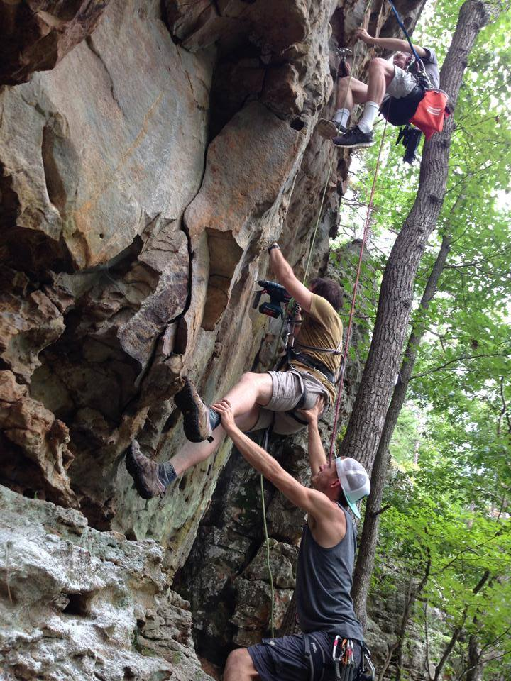 Here, Kyle supports Aaron as he drills holes for a route at Jamestown Crag. Nathan, the eldest of the three brothers, works above.