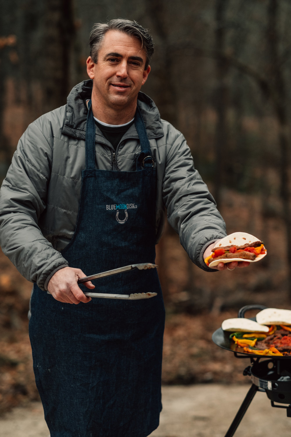 Chuck Peyton, owner and inventor of the Blue Moon Disk, sprinkles Discada Seasoning over deer-steak fajitas during a backyard cookout. The all-purpose seasoning includes a custom blend of spices that brings out the savory flavor of any dish.