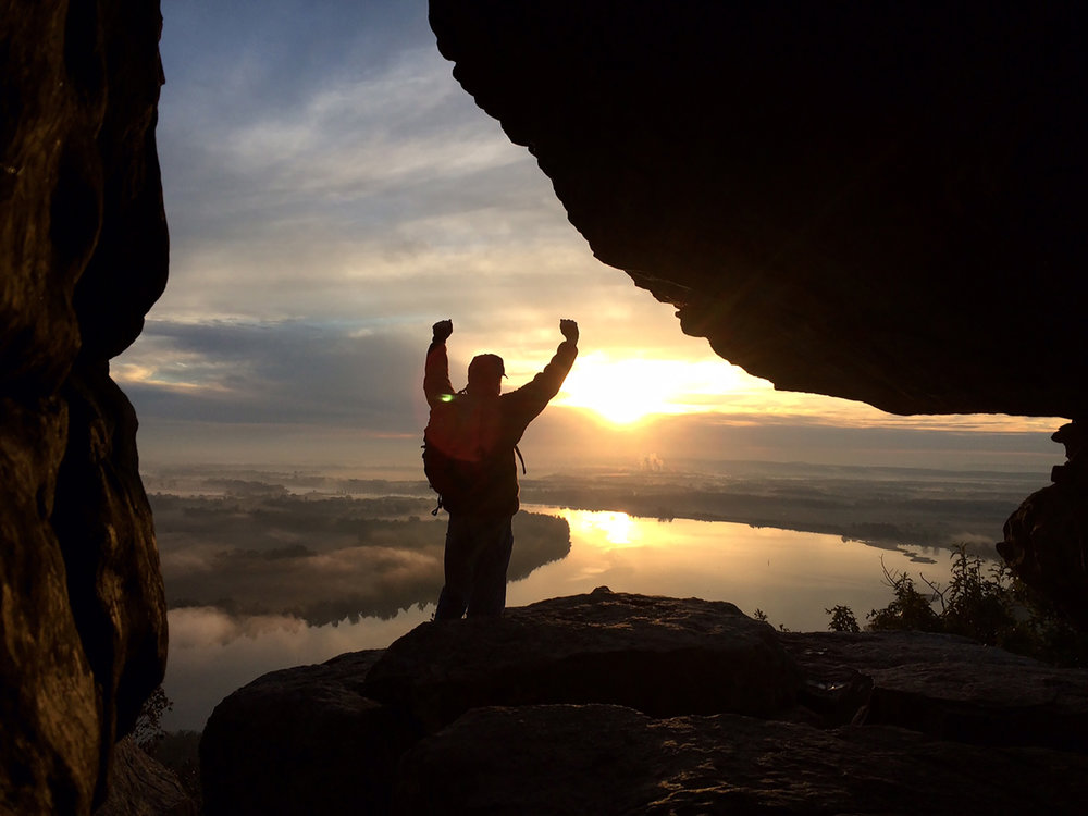 A hiker greets the day at Petit Jean State Park, the state's first and, arguably, still the best offering hiking, fishing, waterfall and a spectacular lodge.