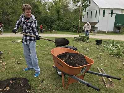 Antioch student Alex Wragg shovels soil at Agraria.