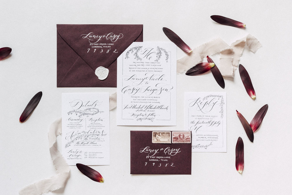 Burgundy wedding invitation suite with custom calligraphy and dainty leaf details.