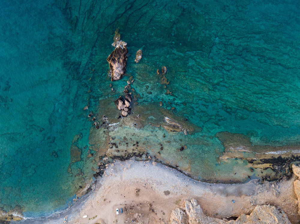 Drone Overhead at Likos. Can you see me? I'm above the cars close to the water, the speck of black on the grey rock by the water.