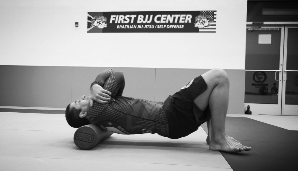 Professor Suyan Queiroz using the foam roller at First BJJ.